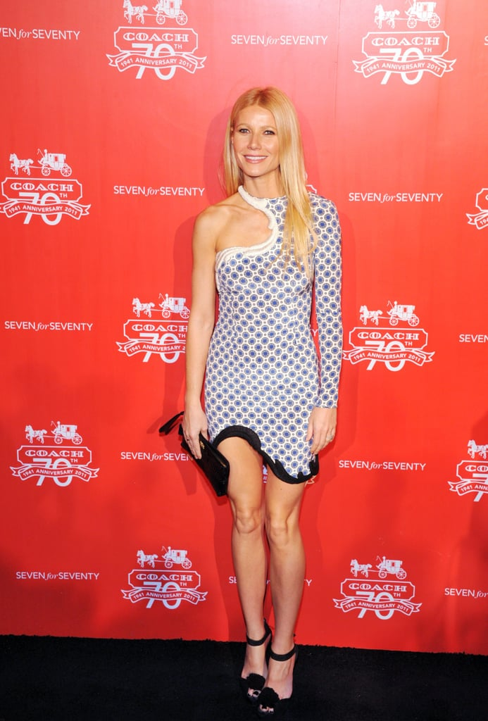 Gwyneth celebrated Coach's 70th anniversary in a printed one-sleeved Stella McCartney number. She accessorized her party style with pom-pom ankle-strap sandals and a textured Coach clutch.