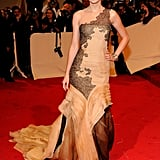 A theatrical nude and black lace couture gown by J. Mendel, featuring soft, hand-frayed organza layers, for the 2011 Met Gala.