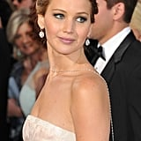 A part-less updo on Jennifer Lawrence allowed a simple set of earrings and a long chain necklace to really sparkle.