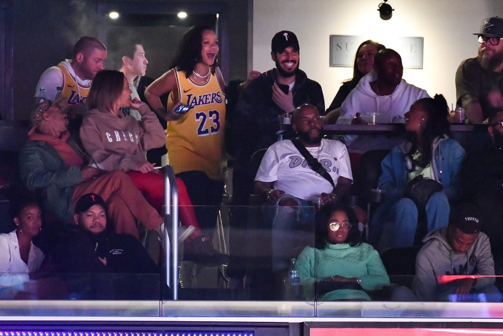 """In the sports world, there's a very plausible theory about the """"Drake curse"""" — meaning, whenever he roots for a team, the team loses (the Toronto Raptors, Alabama football, Kentucky basketball, the list goes on). But Rihanna, on the other hand, she's a blessing in sports, or at least for the Los Angeles Lakers on Thursday night. The 31-year-old superstar attended a very critical game versus the Houston Rockets, where the Lakers came back from a 19-point deficit and won the game, coming one step closer to their playoff goals. The MVP of the night was Rihanna, who celebrated her birthday (which was on Feb. 20) in a suite with a group of friends and her smoking-hot boyfriend, Hassan Jameel.  Rihanna and the Saudi billionaire have reportedly been dating since June 2017, and despite a handful of low-key appearances together, they're relatively private about their relationship. With their good luck in the Staples Center, we have a feeling LeBron James might request their presence at a few upcoming games. ICYMI, Rihanna's been a serious LeBron fan for years, even when he was on the Cavaliers! Rihanna represented the team wearing LeBron's jersey, but it wouldn't be a birthday without a present from the Laker Lords — they gifted her a """"BADGALRIRI"""" jersey! How do we get one of those? Ahead, see Rihanna and her crew at the game, including a few glowing photos of her and Hassan's sweet relationship.      Related:                                                                                                           7 Famous Men Who've Been Lucky Enough to Score a Date With Rihanna"""