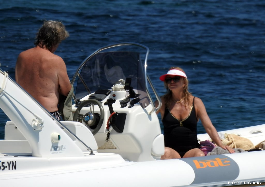"""Goldie Hawn and Kurt Russell jetted off to Greece for a romantic getaway this week, and on Thursday, the longtime couple was spotted relaxing on a boat in the middle of the Mediterranean; Goldie sported a black one-piece and visor as she sat shotgun while shirtless Kurt steered the ship — doesn't their outing kind of give you Overboard flashbacks?      Related:                                                                                                           20 Overboard GIFs That Prove It Will Never Get Old               Kurt and Goldie have a lot to celebrate these days and are certainly deserving of a nice vacation. In April, they rang in their 34th anniversary and just weeks later they were honored with matching stars on the Hollywood Walk of Fame. Goldie shared a photo of herself getting a workout in on Instagram Friday morning; she lifted a water bottle while posing in front of a mural, writing, """"I know will never be like her but. . .never give up!""""      Related:                                                                                                           Maybe It's Time to Stop Asking Goldie Hawn Why She Hasn't Married Kurt Russell"""