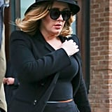 Adele added a little flair to her simple black jumpsuit by styling it with a brimmed hat, sunglasses, a black jacket, and a thin belt that added a pop of color.