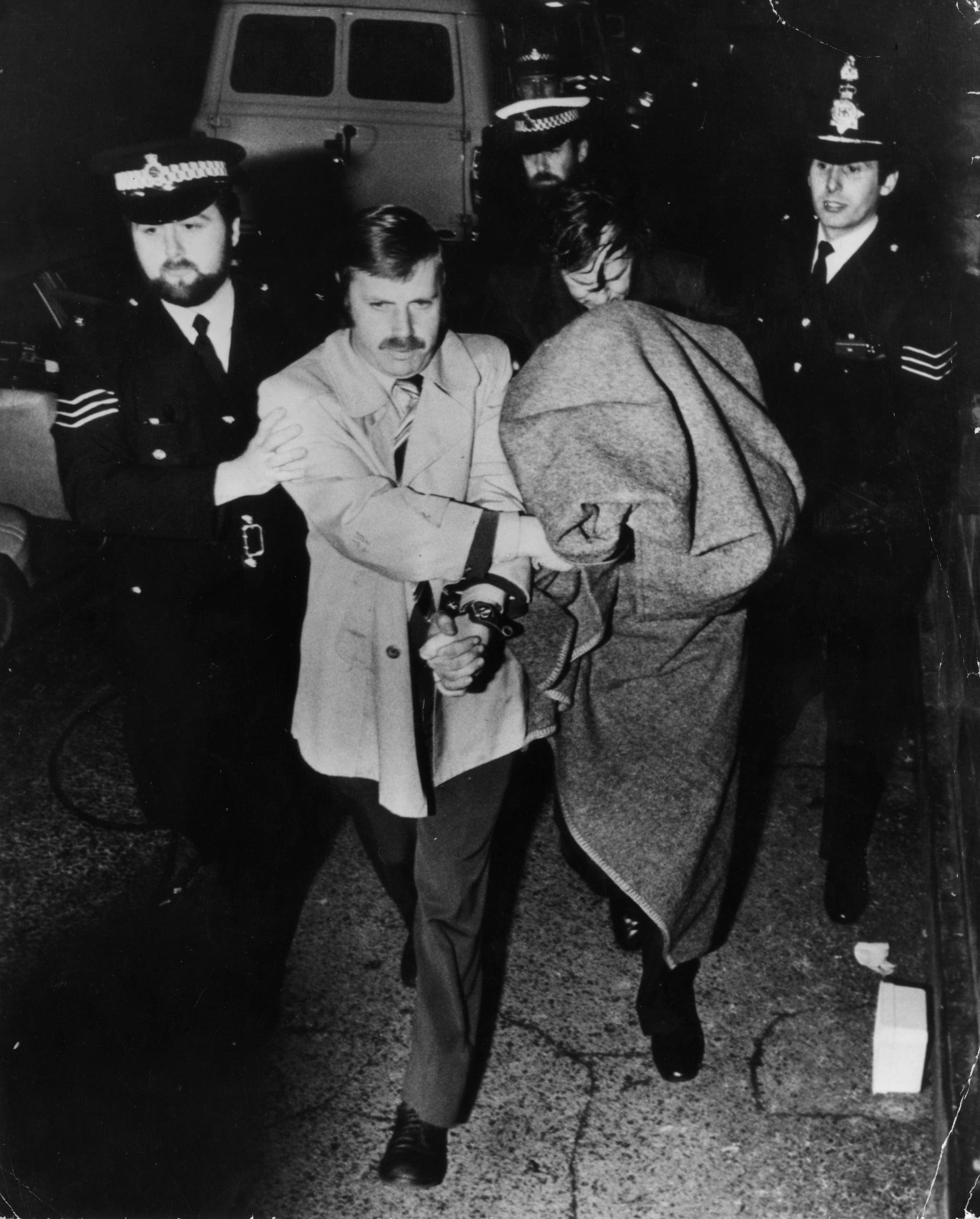 Police leading murderer Peter Sutcliffe, known as the Yorkshire Ripper, into Dewsbury Court under a blanket.   (Photo by Keystone/Getty Images)