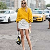 Play with white and yellow when you tuck your cozy jumper into a distressed mini. Relax the look with slingback flats and an easy bag.