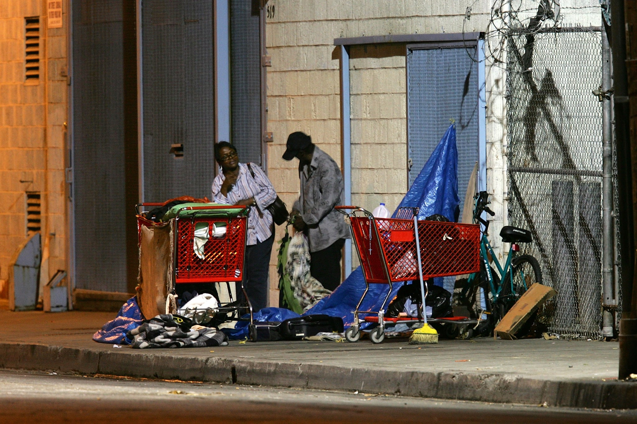 LOS ANGELES, CA - OCTOBER 12:  A homeless couple gets up before dawn to dismantle their encampment before businesses open October 12, 2007 in the downtown Skid Row area of Los Angeles, California. Los Angeles city officials recently settled a 2003 lawsuit brought by advocates for homeless skid row residents who complained of being arrested for sleeping on sidewalks, despite having nowhere else to go. Under the new deal, people can sleep on Los Angeles sidewalks between 9 p.m. to 6 a.m. as long as they do not block doorways or driveways, or completely block the sidewalk. Los Angeles is often referred to as the homeless capital of the nation because of its estimated 40,144 people living on city streets and 73,000 homeless spread across the county, according to recent figures attributed to the Los Angeles Homeless Services Authority, The 73,000 homeless include 10,000 minors, 24,505 people suffering from a mental illness, 8,453 military veterans, and nearly 7,200 victims of domestic abuse.  (Photo by David McNew/Getty Images)