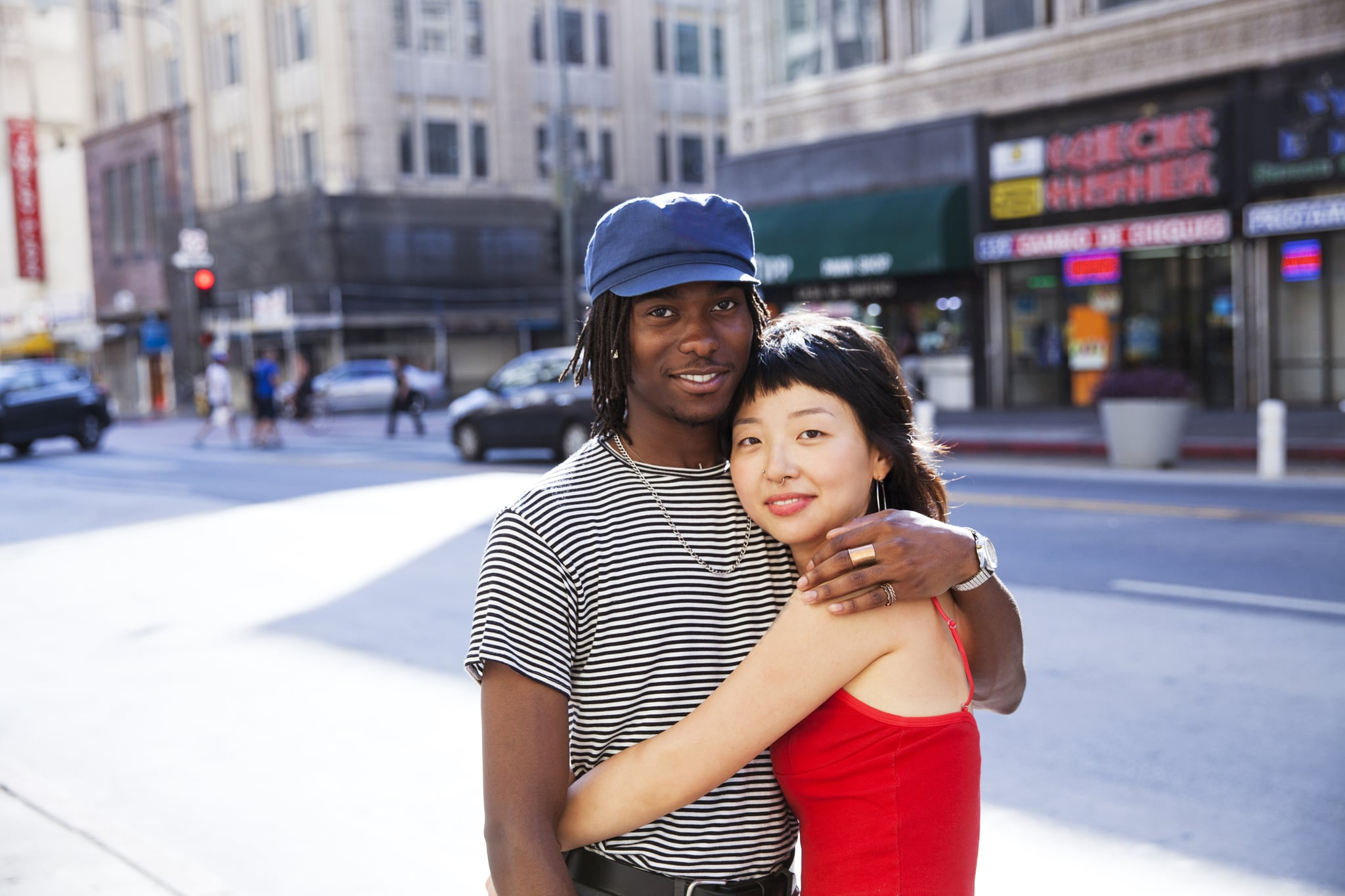 a young couple showing affection while looking at the camera and smiling with a city street scene in the background