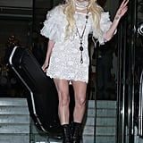 Wearing a white lace dress, black Pleaser boots, and a pink hat.