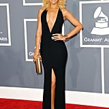 Rihanna set the Grammys red carpet on fire in this sexy black Giorgio Armani gown with a plunging neckline and thigh-high slit. She accessorized with a gold Jimmy Choo clutch and Christian Louboutin Bis un Bout pumps.