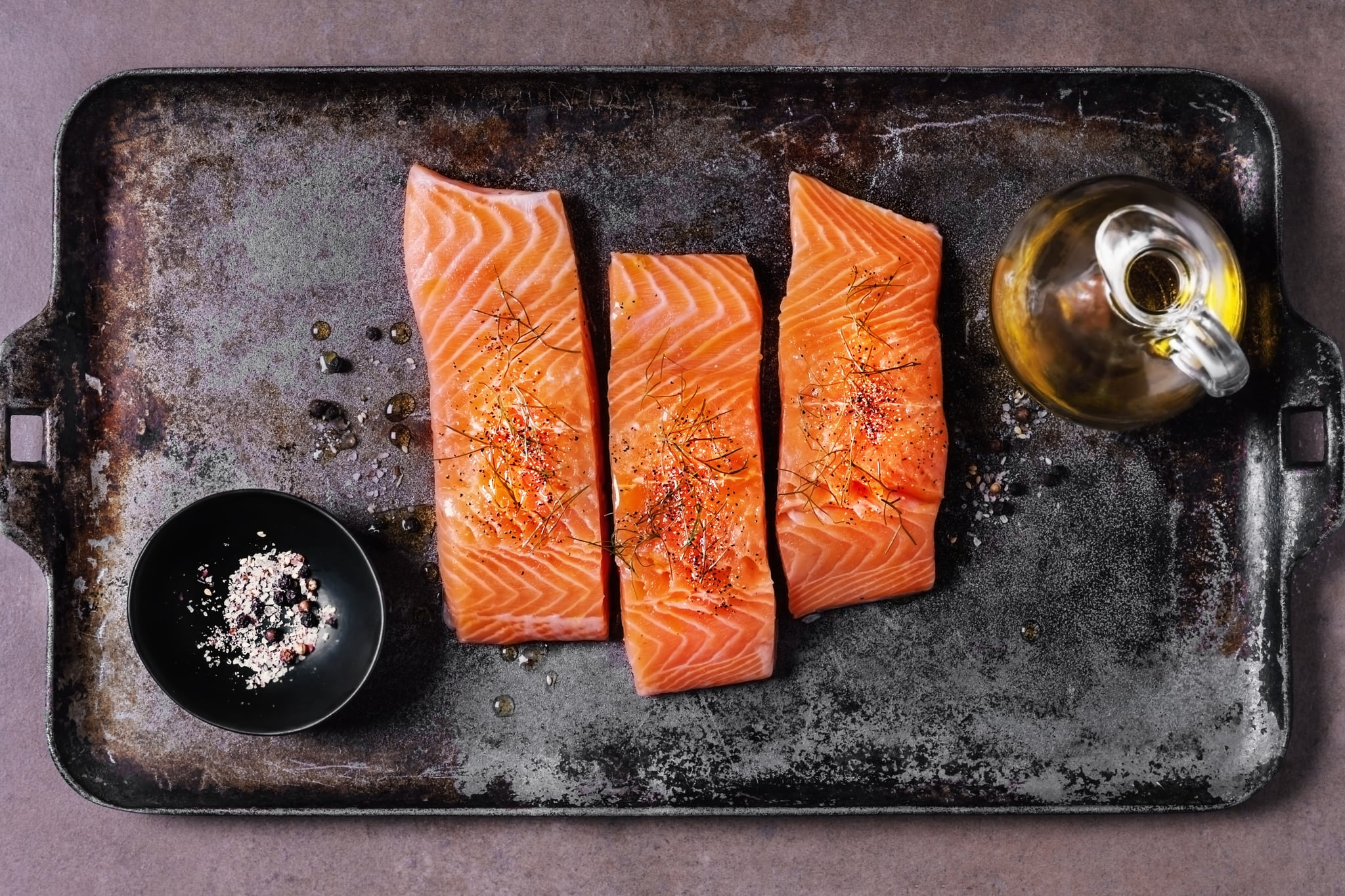 Slices of fresh salmon with spices and olive oil on a metal tray