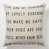 """Your friend will think of you every time she cozies up on the couch next to this Sugarboo """"You Are My Sunshine"""" Pillow ($198)."""