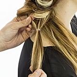 Working down the same ponytail, repeat the process you just completed: secure strands with an elastic, turn that new ponytail inside out, and pancake the base. Repeat this on that one section until you have about two inches of hair left. Then backcomb these strands, adding texture and volume to the braid.