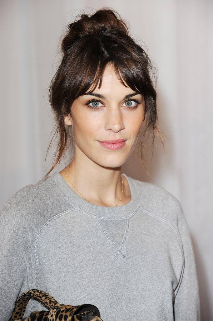 Alexa Chung wore her hair up in a high bun to attend the Mulberry show during LFW.