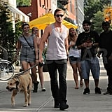 Ryan Gosling walking his dog as fans smile behind him.