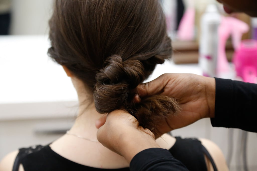 Loosely braid the ponytail and wrap it up into a chignon. If there are any short hairs around the nape that escaped the bun, use Aveda Control Paste ($24) to brush up and hold the wispy strands (bobby pins also work, if your hair is extra-uncooperative).