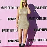 Kylie Jenner wearing a PrettyLittleThing metallic mini dress and boots at the Pretty Little Playground x Paper Magazine party.