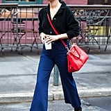 "We love the way the singer and actress wore Stuart Weitzman's popular ""Clinger"" boots under her indigo kick-flare jeans with a laidback sweater tucked into its high waist. She perfectly added a pop of color with the Coach bag she designed and named after her sister, Grace."