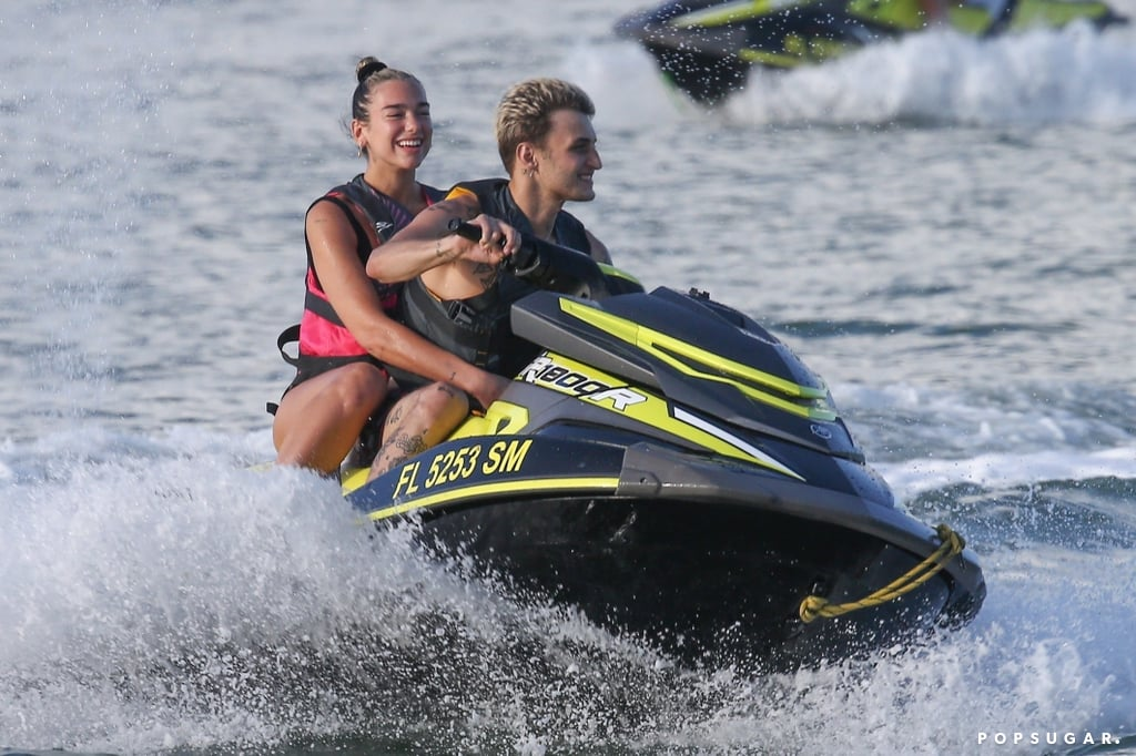 "Dua Lipa and Anwar Hadid are having a happy new year, indeed! On Jan. 3, the couple set out on a jet ski for a fun ocean adventure in Miami. They took turns steering the watercraft, making big splashes and sharing a few laughs. The 24-year-old ""Don't Start Now"" singer and 20-year-old model kept safety first as they wore life vests over their swimwear. The previous day, they were spotted making out on a deck and showing off their playful sides as Anwar gave his girlfriend a piggy-back ride. They've been taking in the warm weather since the holidays and were seen smooching in the Sunshine State on Dec. 31. They appeared to enjoy each other's company, flashing bright smiles and holding hands. Naturally, Dua stunned in an animal-print bikini and Anwar sported a graphic tee before going shirtless. They later rang in the new year at a party where Dua modeled a glimmering silver dress and Anwar wore a casual ensemble. The pair first sparked romance rumors in July when they hung out at the British Summer Time Hyde Park music festival in London. Dua was previously dating chef and model Isaac Carew, and Anwar — Gigi and Bella Hadid's younger brother — was linked to Kendall Jenner. Since then, Dua and Anwar have shared a handful of adorable moments together, including their Malibu getaway in August and their red carpet debut as a couple at the American Music Awards in November. Look ahead to see more photos from their recent Miami escapade!      Related:                                                                                                           Let's Talk About How Freaking Cute Dua Lipa and Anwar Hadid Are Together"