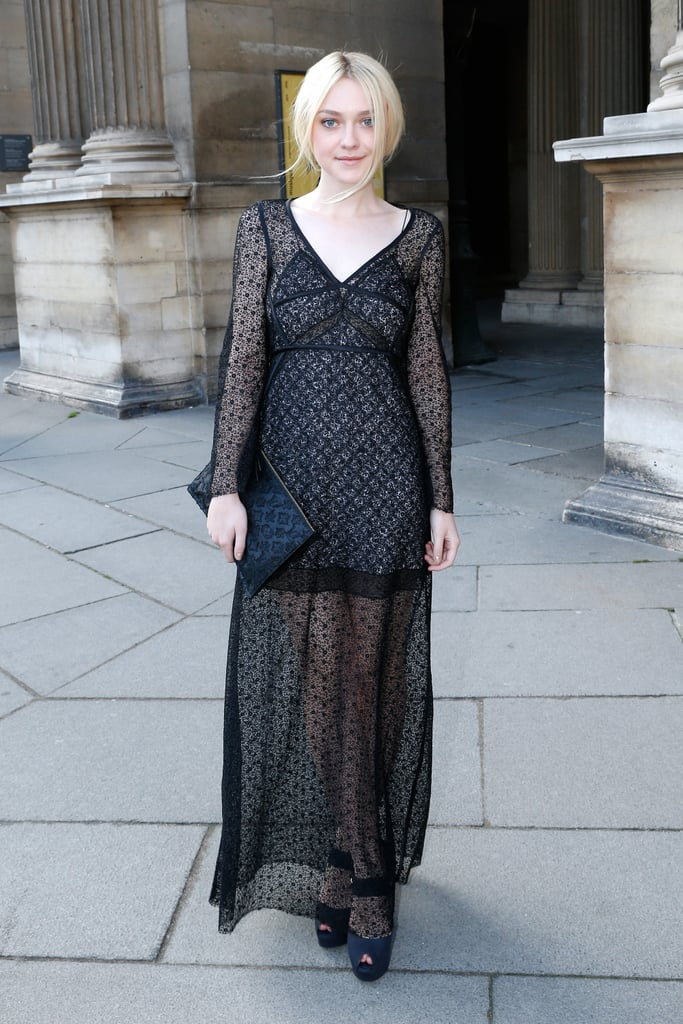 En route to Louis Vuitton, Dakota Fanning posed in a sheer maxi dress with a Louis Vuitton clutch.