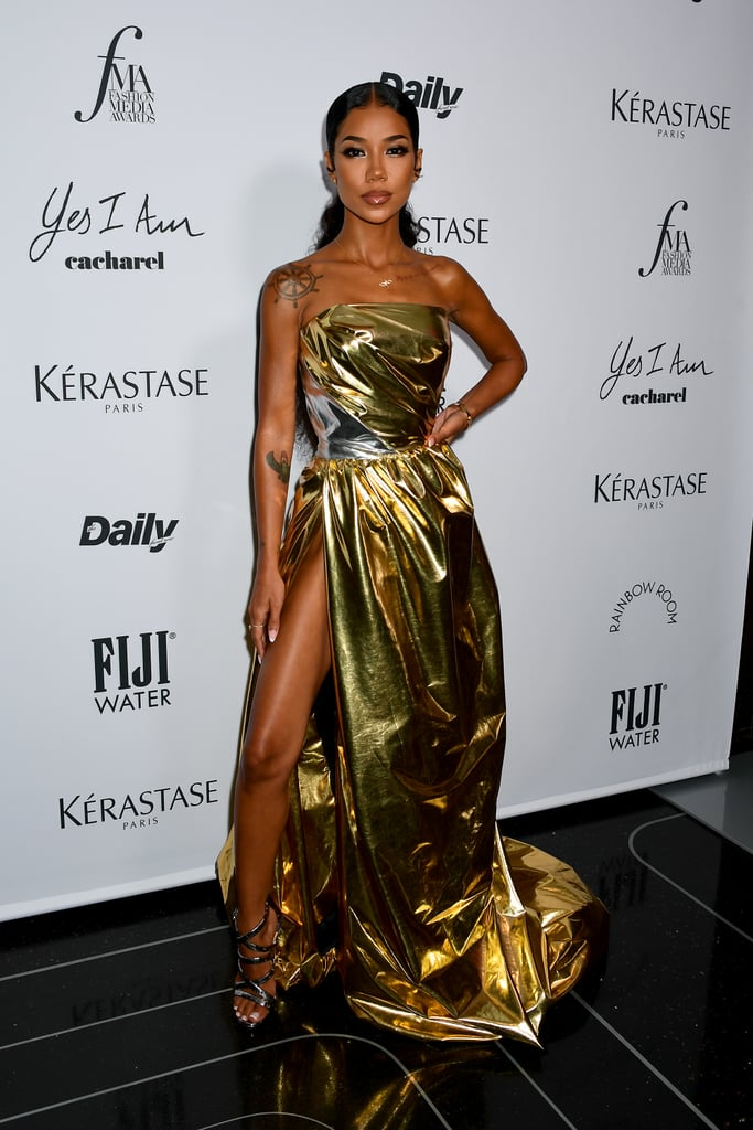 """Jhené Aiko could write a book on commanding a red carpet — just look at her latest. At the Daily Front Row's annual award show at New York Fashion Week on Thursday, the singer posed in a metallic gold dress so major, she looked like a trophy come to life. Her goddess-like gown is by Toni Maticevski, which she teamed with gold Sydney Evan jewellery and strappy Christian Louboutin stilettos to match, with the help of stylist Icon Billingsley. Though the metallic in itself was a showstopper, the daring mile-high slit on Jhené's dress might have been the highlight, showing off her legs for days. """"a living light ✨,"""" she wrote alongside photos from the event on her Instagram afterwards. I mean, I'd say that's a pretty accurate description of her radiating look. Get a closer look at the details on the singer's outfit ahead.       Related:                                                                                                           Surprise, Darlings! Cruella de Vil Is Actually the Biggest Trendsetter at NYFW This Year"""