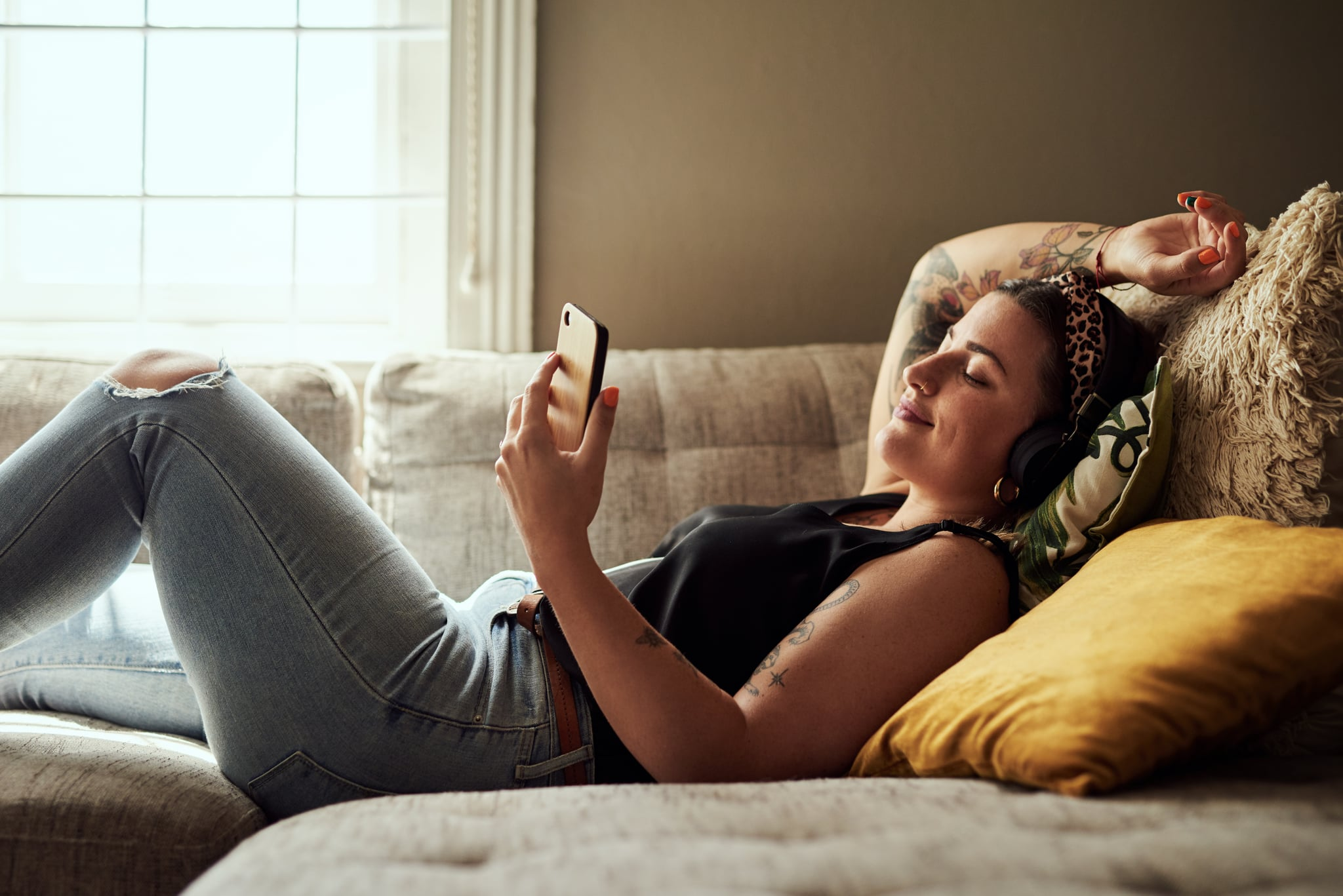 Shot of a young woman using a smartphone and headphones on the sofa at home