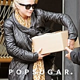Mary-Kate Olsen carried a heavy box out of a store.