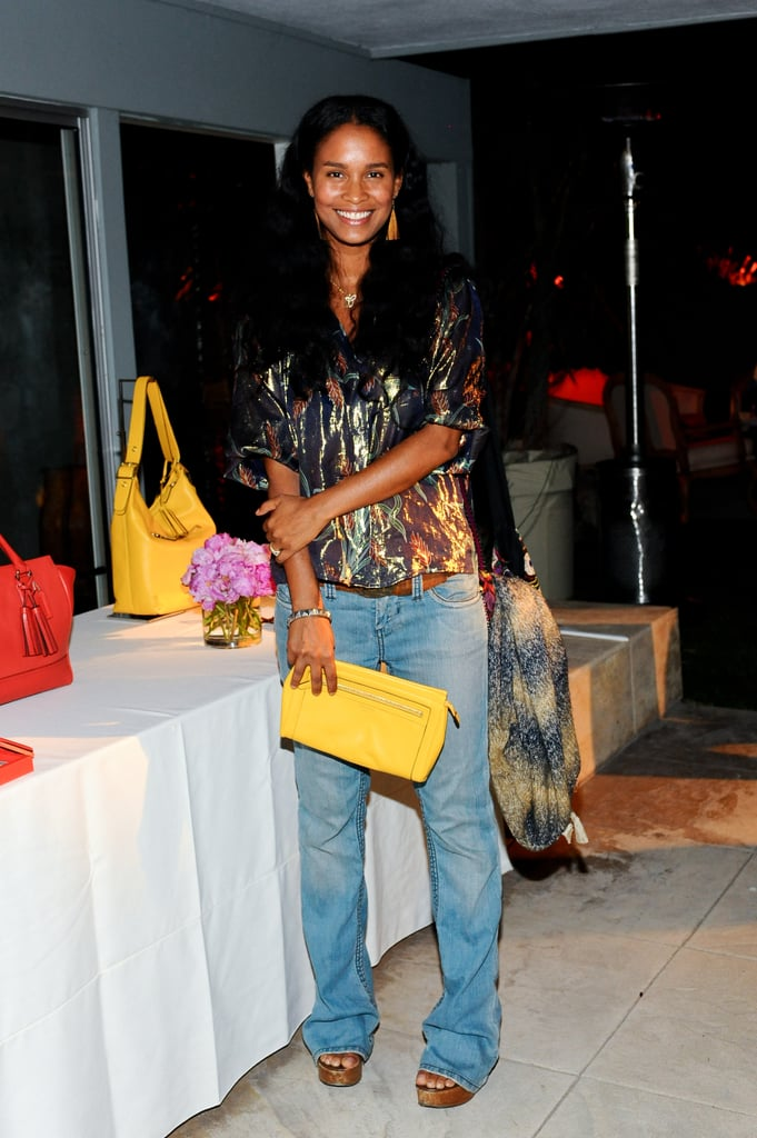 Joy Bryant dressed up jeans with a metallic top and a brilliant yellow clutch.