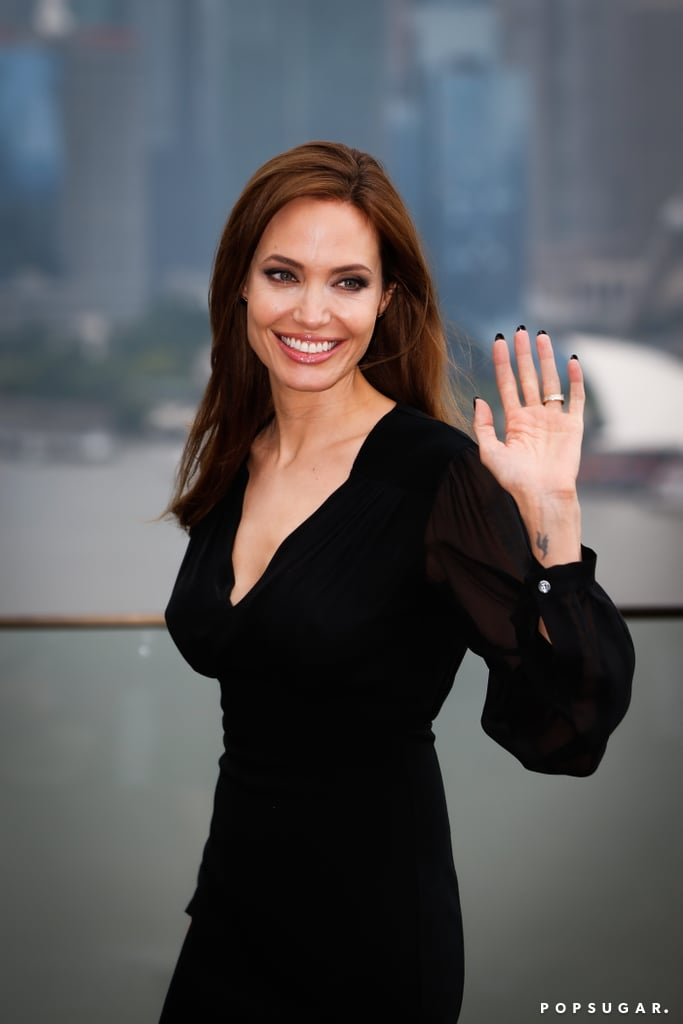Angelina Jolie waved to fans during a press stop for Maleficent in Shanghai on Tuesday.