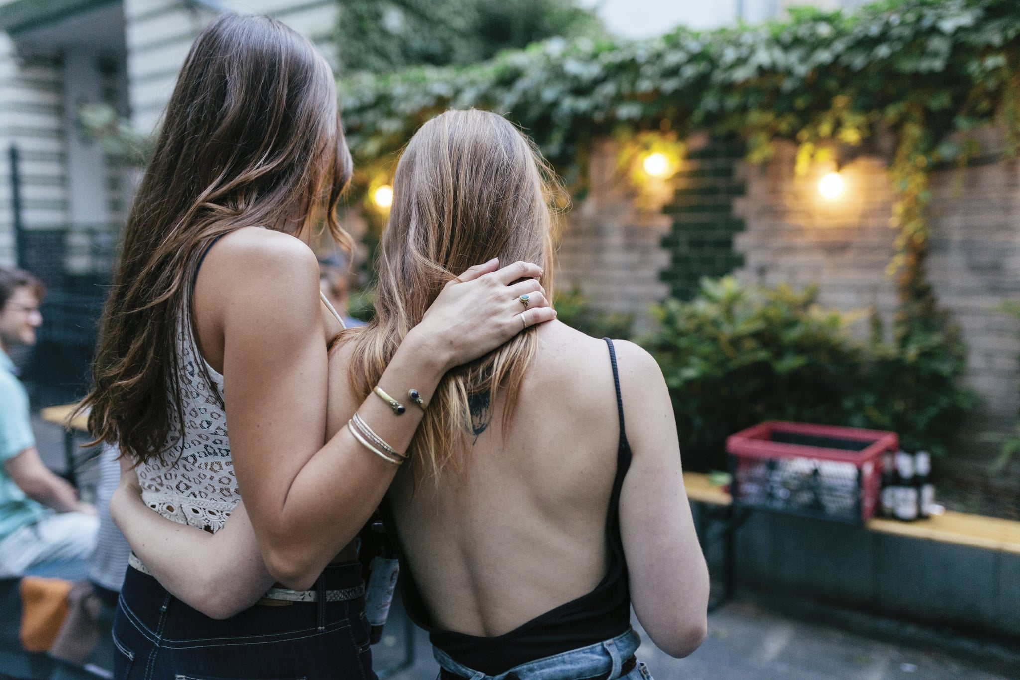 Two Friends Embracing While Waiting For Barbecue To Warm Up