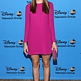 Christa B. Allen posed in a fuchsia shift dress and a pair of metallic heels.