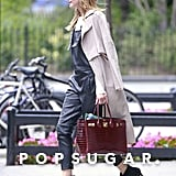 Dressing up leather overalls like a pair of great leather pants, Olivia slipped on a pair of ankle booties, a long-sleeved blouse, and a trench balanced nonchalantly across her shoulders to take the look to the next level.