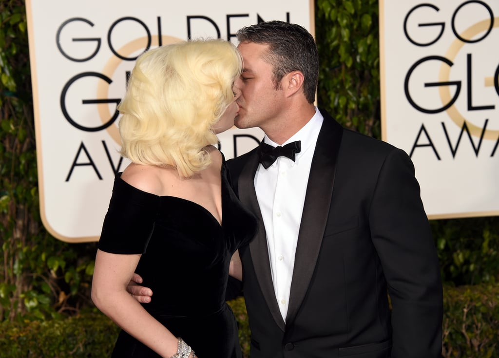 Lady Gaga and her fiancé, Taylor Kinney, were the picture of Old Hollywood royalty at the Golden Globes in LA on Sunday. The couple walked the red carpet together and stole a few kisses while posing for photos. Gaga was joined at the event by her American Horror Story: Hotel cast members; Gaga is nominated for an award during tonight's ceremony.  Taylor and Gaga's public display comes just days after their supersteamy V Magazine cover hit the Internet; along with the nude snap, their love was in the news after Taylor thanked Gaga during his acceptance speech at the People's Choice Awards last week, where he picked up the honor of favorite dramatic TV actor. Keep reading to see Gaga and Taylor at the Globes, and then find out everything we know about their upcoming wedding.