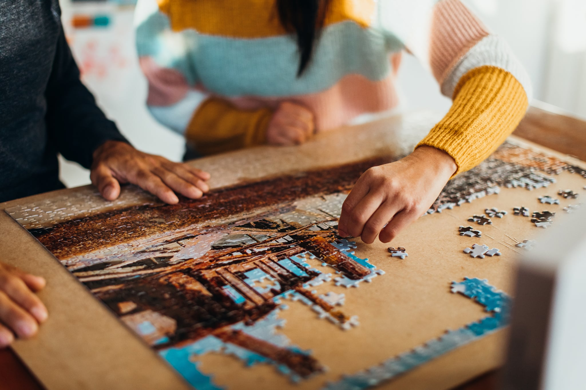 Close up shot of the hands of a couple doing a jigsaw puzzle in their kitchen, shot from in front
