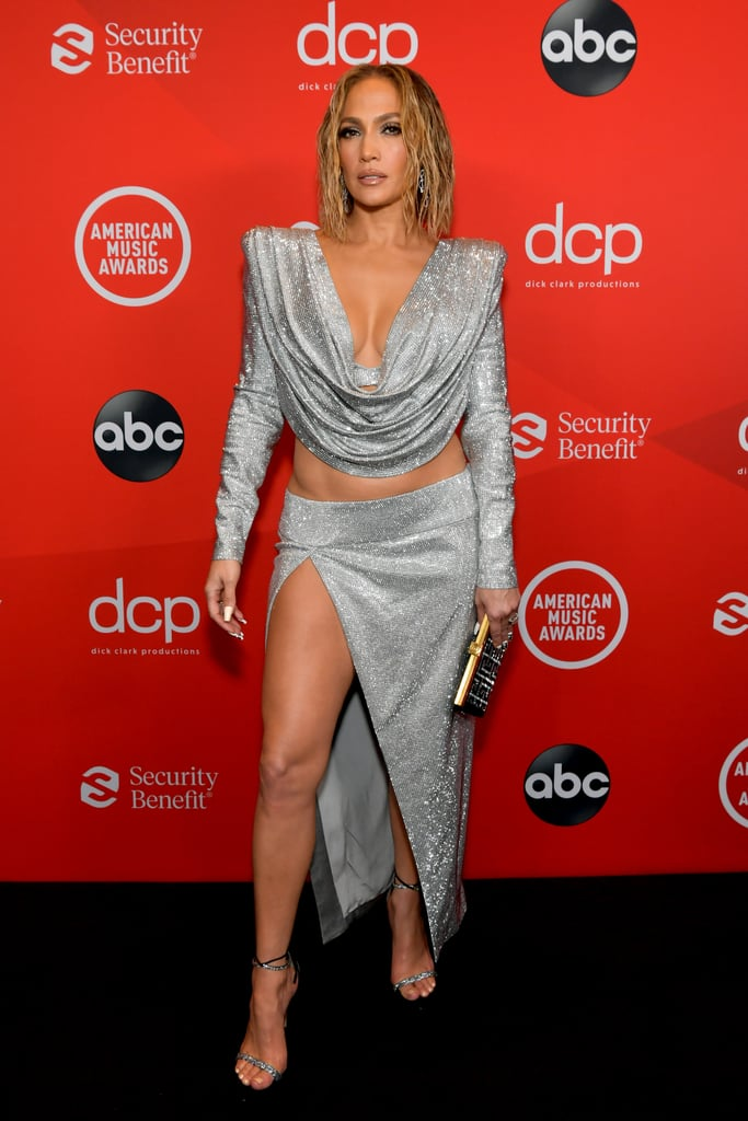 "Jennifer Lopez showed up to the American Music Awards on Sunday night looking like a shining goddess in silver. The ""Pa Ti"" singer made an appearance before her performance with Maluma, and naturally, she chose a jaw-dropping outfit for the occasion. Jennifer posed for photos in a sparkling cropped set with structured shoulders and a plunging neckline. She paired the set with jeweled heels and a glittering clutch — how chic! She's certainly no stranger to a sleek metallic look, but she continues to find fresh and modern ways to shake things up. Keep reading to see even more of Jennifer's showstopping look from the award show.       Related:                                                                                                           Jennifer Lopez Looks Like the Icon She Is in This Stunning Christian Siriano Dress"
