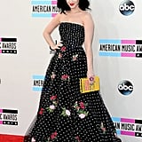 """Katy Perry was one of the first stars to show up to the American Music Awards red carpet, and her look was more ladylike than usual. The singer wore a girlie-yet-grown-up dress – a black polka-dot gown complete with floral appliqués by Oscar de la Renta. She paired the strapless frock with an adorable Olympia Le-Tan """"Webster's New World Handy Pocket Dictionary"""" box clutch."""