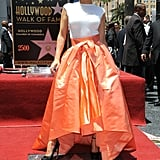 Jennifer Lopez wore a Dior off-white cashmere and silk knitted top with a coral satin skirt for her Hollywood Walk of Fame ceremony. She finished off with H.Stern earrings and Brian Atwood black ankle-strap pumps.