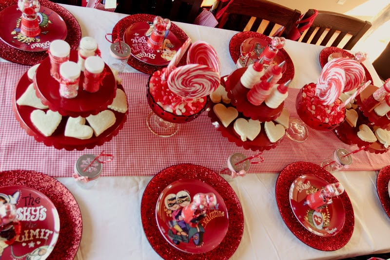 The decorating table was set up with red plates for eating and decorating, cookies waiting to be jazzed up, sprinkles, swirl lollipops, and more fun touches.  Source: Jenny Cookies
