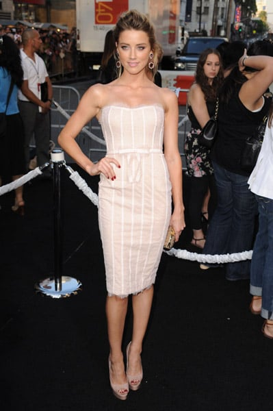 Amber Heard, super femme in a nude strapless lace cocktail Marchesa dress with empire bow detail; her Jimmy Choo clutch and Brian Atwood Wagner pumps complete the lovely look.