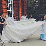 The bride and groom embraced in a passionate kiss as one of her bridesmaids held up the gown's long train.