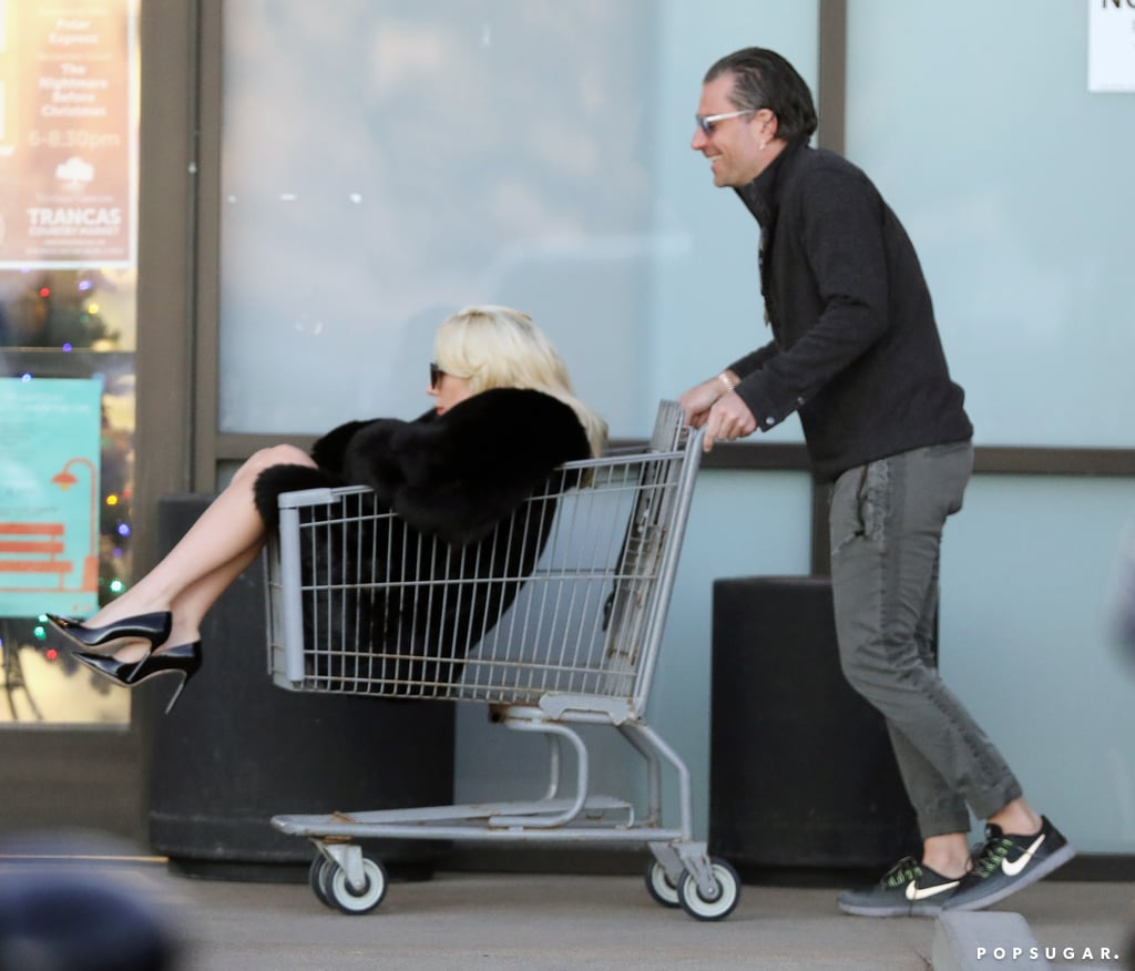 Lady Gaga is a queen, and in case you somehow forgot, her latest outing should remind you. While most people (including celebrities) do their grocery shopping on foot, Gaga proved once again that she isn't like most people when she was photographed casually being pushed around by her fiancé, Christian Carino, in a shopping cart at a grocery store in Malibu, CA, on Thursday. In addition to her unique mode of transportation, Gaga was dressed in a fur coat, a black dress, and matching heels — you know, as one dresses for the occasion.      Related:                                                                                                           14 Times Lady Gaga Was the Most Fascinating Person in 2017               Gaga and Christian first struck up a romance earlier this year and reportedly got engaged over the Summer. It's been a while since we've seen them out together, but from the looks of it, they're doing great.