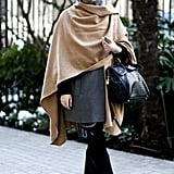 Effortless elegance with a camel scarf tossed over her shoulder and finished with classic black boots.