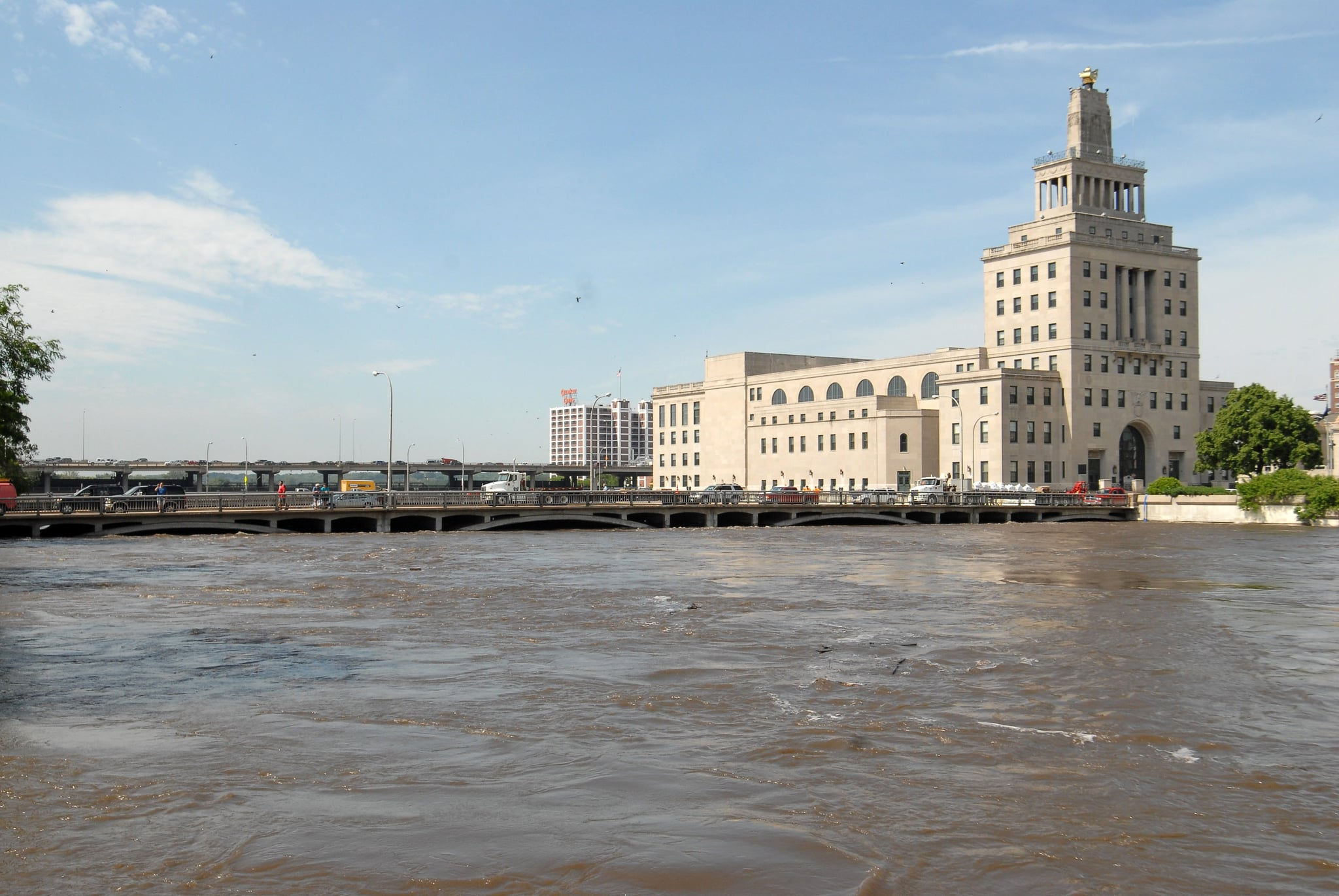 The Federal Building stands on an island next to the rising Cedar River.