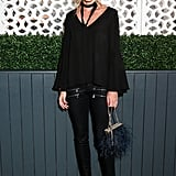 While out celebrating Fashion Week with Vogue and Stuart Weitzman, Olivia gave an all-black outfit intrigue with a skinny scarf, fringed bag, and ankle-strap Stuart Weitzman heels.