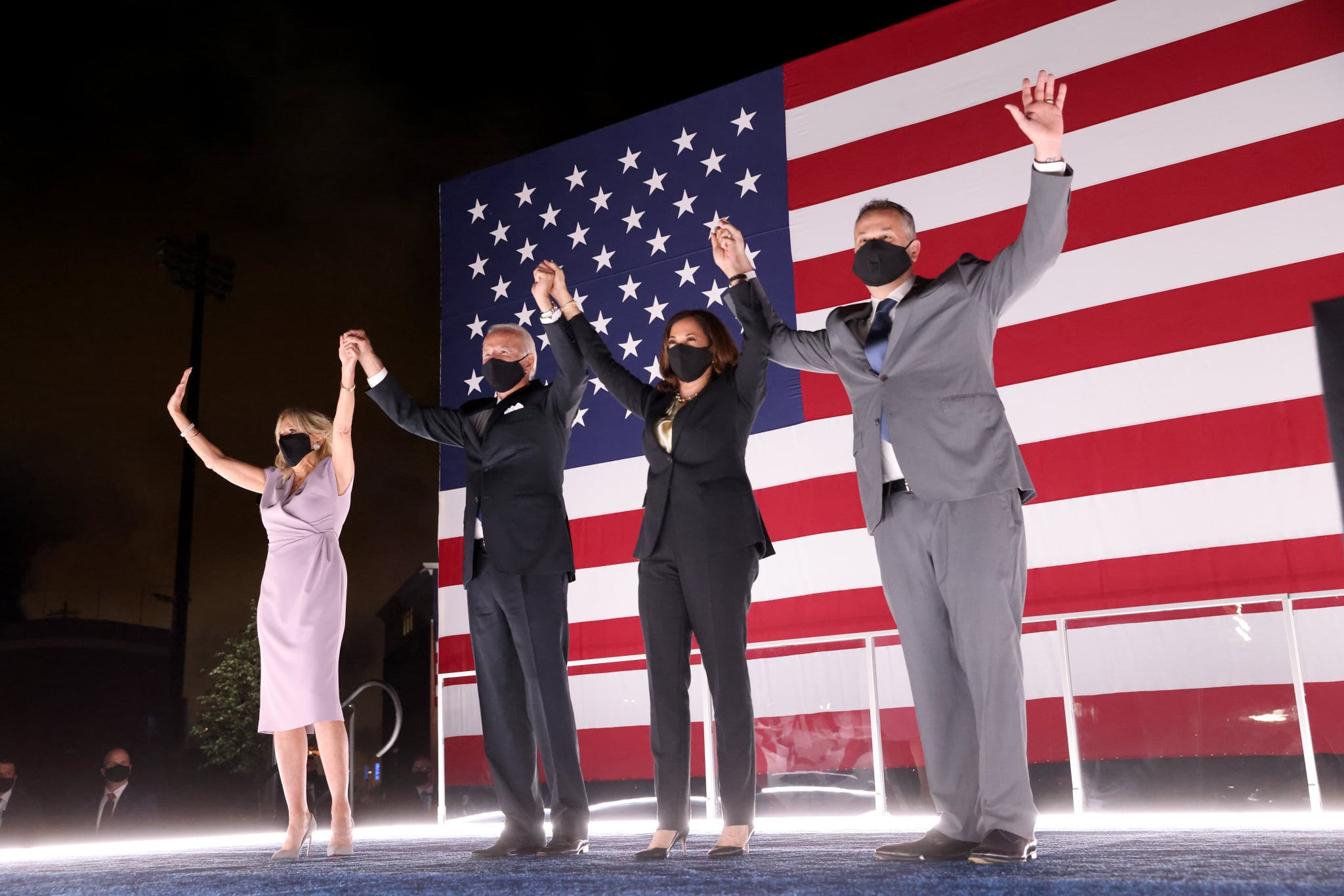 WILMINGTON, DELAWARE - AUGUST 20: Democratic presidential nominee Joe Biden, his wife Dr. Jill Biden, Democratic Vice Presidential nominee Kamala Harris and her husband Douglas Emhoff raise their arms on stage outside the Chase Center after Biden delivered his acceptance speech on the fourth night of the Democratic National Convention from the Chase Center on August 20, 2020 in Wilmington, Delaware. The convention, which was once expected to draw 50,000 people to Milwaukee, Wisconsin, is now taking place virtually due to the coronavirus pandemic. (Photo by Win McNamee/Getty Images)