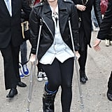 Demi Lovato was still stuck in a cast when she arrived at London Fashion Week on Sunday.