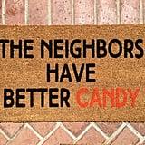 حصيرة باب عليها عبارة The Neighbors Have Better Candy (بسعر 28$ دولار أمريكيّ؛ 103 درهم إماراتيّ/ريال سعوديّ)