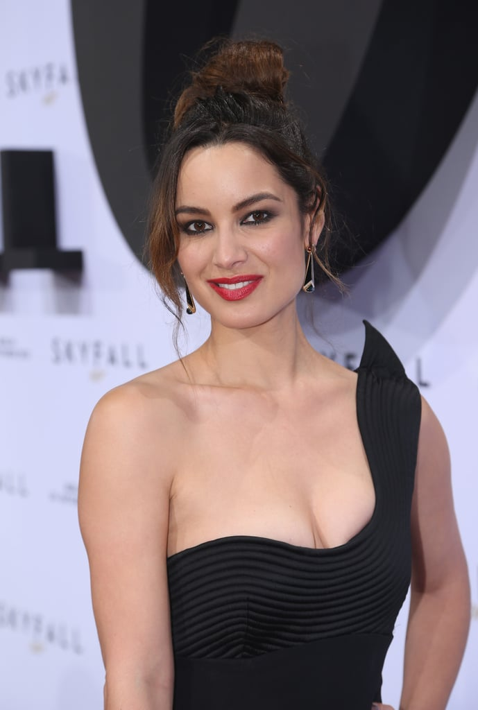 She completed her look with a sexy, tousled updo, drop earrings, and red lip.