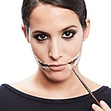 Extend the slit of the lips using a black eyeliner.