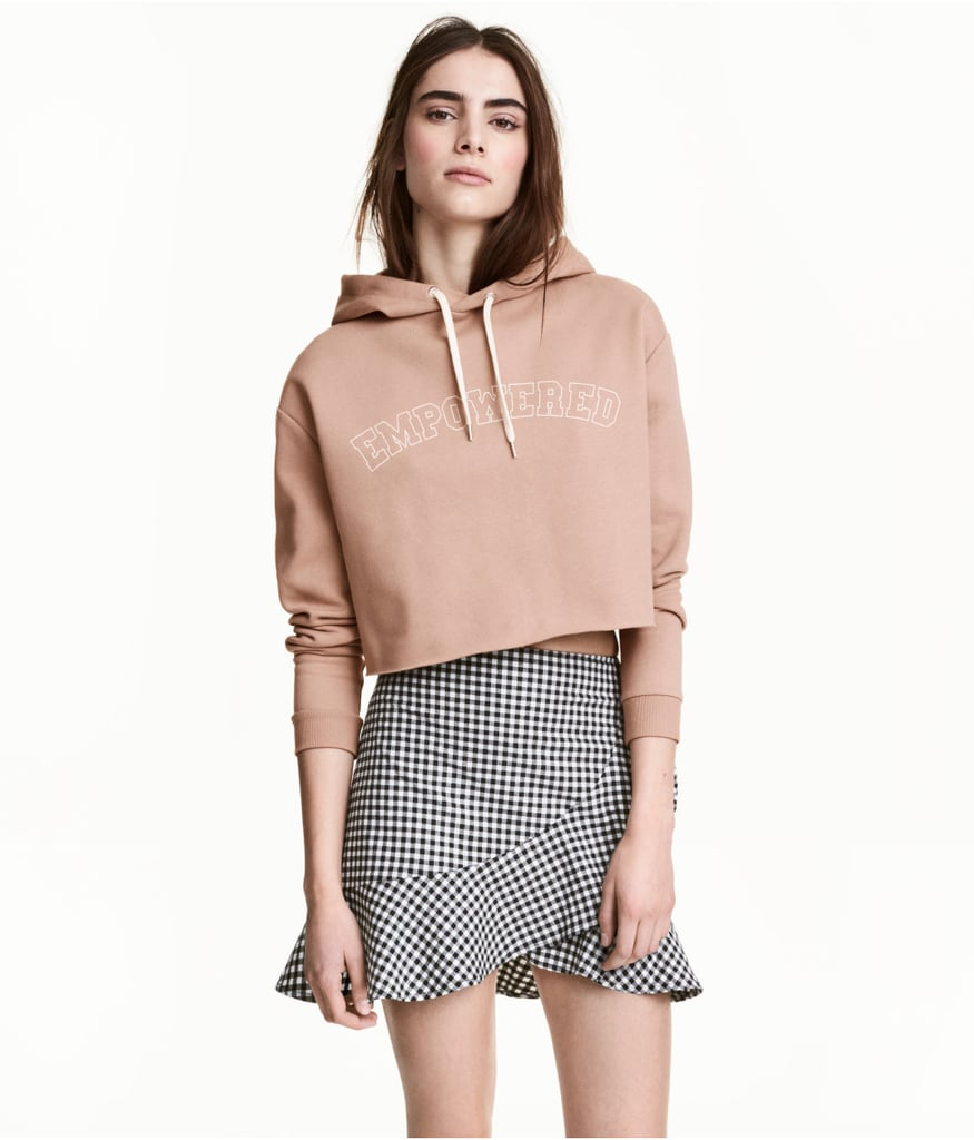 """H&M's Short Hooded Sweatshirt ($25) is offered in a range of colors with a bunch of different graphics. The """"empowered"""" version has a tough appeal and looks cool paired with a miniskirt."""