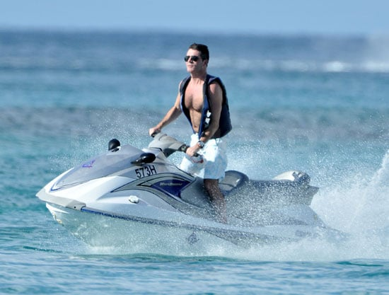 Simon Cowell showed his shirtless physique on a jet ski in Barbados yesterday. He had a little trouble with customs on his way to the Caribbean, having to pay £100 to bring his favourite beer with him. Back in August, Simon got his torso out on holiday in France with Mezhgan Hussainy, earning him a place in the hottest shirtless Brits of the year. On this holiday, Simon is reportedly hanging with his ex-girlfriends Sinitta and Terri Seymour, and Mezhgan will fly out next week to join him. Judging by the grin on Simon's face, he's not too disappointed that his act One Direction didn't win The X Factor.