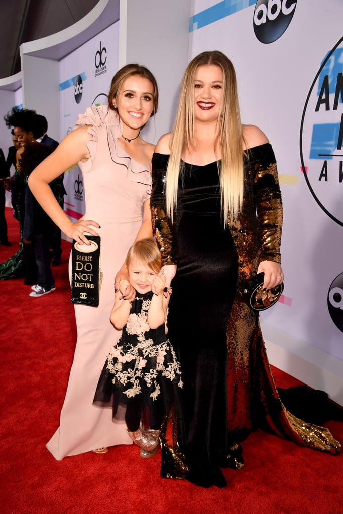 """It was girls' night out for Kelly Clarkson at the American Music Awards in LA on Sunday. The singer, who opened the show alongside Pink with a beautiful rendition of """"Everybody Hurts,"""" hit the red carpet with her 3-year-old daughter, River Rose, and her 16-year-old stepdaughter, Savannah Blackstock, whom she shares with husband Brandon Blackstock. Before taking the stage, Kelly talked to E! News about how she manages being a mum and a singer. """"I think it's any working mum, any working parent's struggle. It's a balancing act. We do our best,"""" she explained, jokingly adding, """"I am sure they will end up in therapy.""""   Kelly also opened up about her upcoming stint on the next season of NBC's The Voice. """"I like that I get to be a coach and not a judge. 'Cause I am not good at judging. But I am really good at coaching and feeling like I have been them."""" Keep reading to see more photos of Kelly's night."""